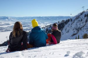People sitting on top of a snowy mountain slope, enjoying the view.